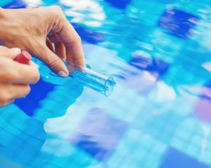 Person testing the pool water.